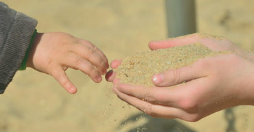 summer-programmes-image-child-reaching-sand-parent